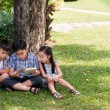 Children sitting under tree — Stock Photo #63672633