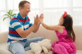Father and daughter playing patty cake — Stock Photo