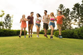 Friends running on summer meadow — Stock Photo
