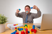 Businessman playing lego in the office — Stock Photo