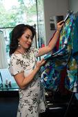 Elegant woman choosing skirt — Stockfoto