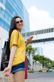 Modern girl with cellphone and shopping bags — Stock Photo