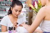 Asian manicurist applying nail polish — Stock Photo