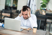 Stressed businessman with  laptop — Stock Photo