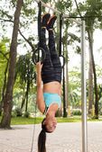 Woman hanging on gymnastic rings — Stock Photo