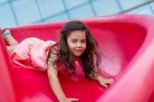 Girl on red slide — Stock Photo