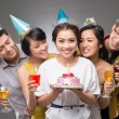 Girl holding a cake with her friends — Stock Photo #69308971