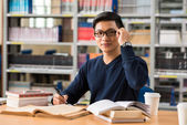 Young man working in a library — Stock Photo