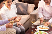 Business colleagues eating and drinking wine — Stock Photo