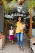 Mother and daughter leaving grocery store — Stock Photo