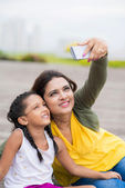 Woman and her daughter taking selfie outdoors — Stock Photo