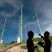 Silhouette of engineers looking at wind turbine site — Stock Photo