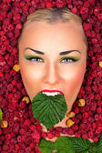 Beautiful face with green leaf raspberry in mouth — Stok fotoğraf