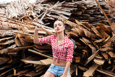 Woman ax in hand in a plaid shirt — Stock Photo