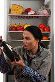 Dirty beggar hungry stares at the bottle of wine — Stock Photo