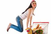 Beautiful woman with a supermarket trolley in a jump — Stock Photo