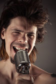 Man with disheveled hair singing into retro microphone — Stock Photo
