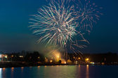 Fireworks at night over water — Stock Photo