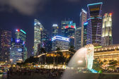 The Merlion fountain lit up at night on July 09, 2015 in Singapore. Singapore is a world famous tourist city with highly developed economic infrastructure. — Stock Photo