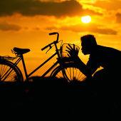 Silhouette of a man kissing a bike — Stock Photo