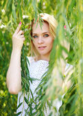 Close-up portrait blond young woman in the branches of a willow — Stock Photo