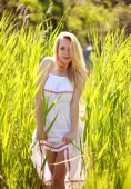 Sensual young woman in white dress posing in green reeds — Stockfoto