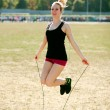 Young sporty woman workout, jumping over rope — Stock Photo #53816491