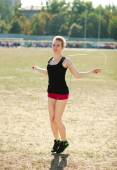 Young sporty woman workout, jumping over rope — Stock Photo