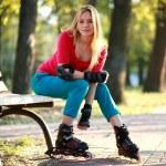schöne junge Frau in Rollschuhe sitzt auf der Parkbank — Stockfoto #54045077