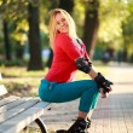schöne junge Frau in Rollschuhe sitzt auf der Parkbank — Stockfoto #54048453
