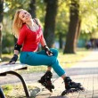 Beautiful young woman in roller skates sitting on park bench — Stock Photo #54044963