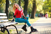 Beautiful young woman in roller skates sitting on park bench — Stock Photo