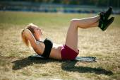 Young woman doing press fitness exercise for stomach muscles — ストック写真