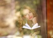 Smiling woman with book at home, view through window glass — Stock Photo