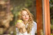 Pensive woman drinking coffee at home, looking out the window — Stok fotoğraf