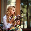 Attractive young woman reading book while drinking coffee — Stock Photo #56079179
