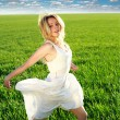 Happy girl running on the green blossoming field under blue sky  — Stock Photo #67758657