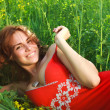 Smiling sexy young woman lying in the grass in a red dress — Stock Photo #67758661