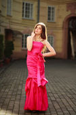 Girl in luxurious long pink dress on street of old town — Stock Photo