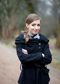 Smiling young woman in a black coat in the autumn park — Stock Photo
