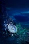 闹钟在晚上草地上 — 图库照片