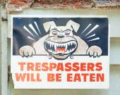 Sign stating TRESPASSERS WILL BE EATEN with Angry Dog Symbol — Stockfoto