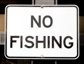 Old Faded White and Black Sign Stating NO FISHING — Stock Photo