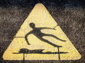 Triangular Hazard Symbol of Man Slipping on Water and Falling — Stock Photo