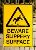 Hazard Sign: BEWARE SLIPPERY SURFACE with picture of man falling — Stock Photo