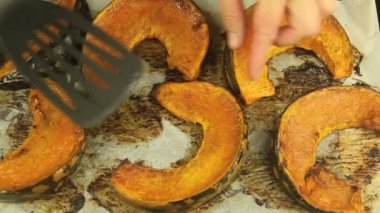 Turning slices of baked pumpkin — Stock Video