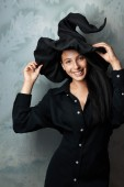 Cheerful girl in witch costume smiling — Stock Photo