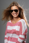 Woman laughing with off sunglasses — Stock Photo