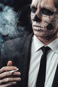 Portrait businessman smoking with makeup skeleton — Foto Stock