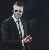 Portrait businessman smoking with makeup skeleton — Photo